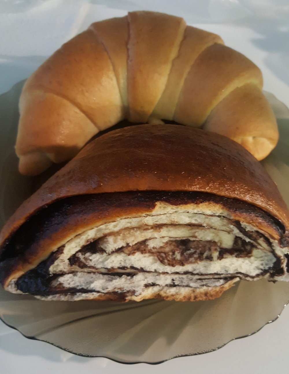 Pictured: Top: Crescent-shaped bread (Kifli), Bottom: Layered swirl bread with chocolate filling. Photographer: Ruxandra Chitac.