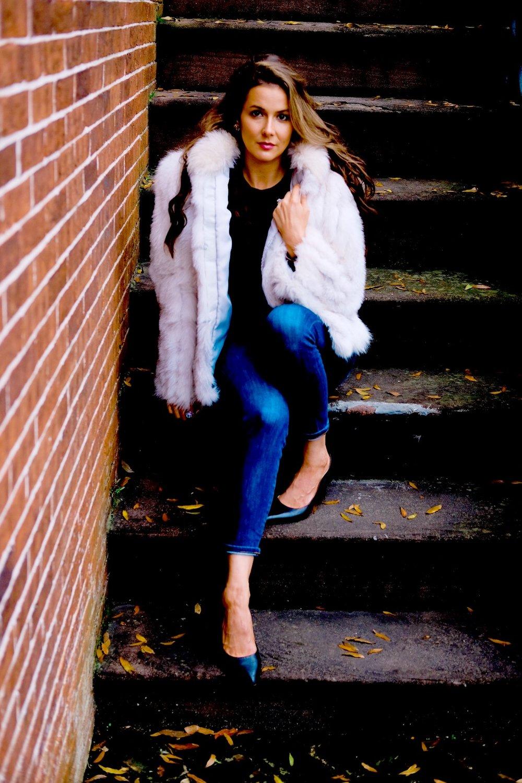 Brenna Lauren Michaels in faux fox fur coat sitting on steps in Savannah GA