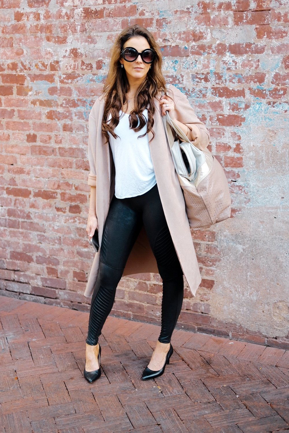 Brenna Lauren Michaels in Spanx moto leather leggings, pink suede duster, and black pumps
