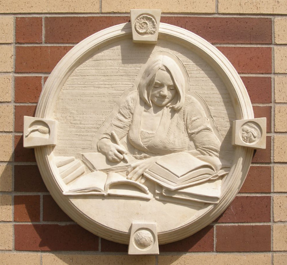 "The Reader III - St. James, MN, cast stone installation, 36"" diameter."