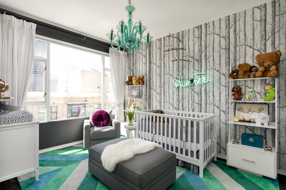 With kids, it's essential to be able to quickly toss and hide all the toys that eventually get left around the room. An over-sized storage ottoman is perfect for not only toys, but also nice for propping your feet up during story time. It's perfect to sit on during sleep training and midnight feedings.   The vibrant blue/green chandelier mimics the rug and brings in a touch of elegance.