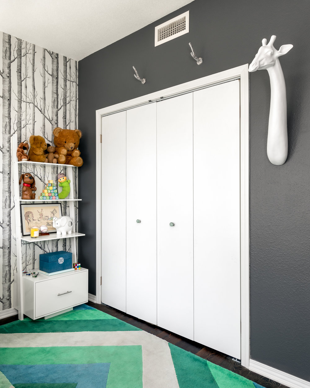 "Little details like the blue/green glass closet knobs help to bring in more of the color palette, adding to the overall look. Handy branch hooks hang above the closet door and the curious giraffe mounted to the wall is gazing toward the crib. Babies love busy patterns so we chose the oak tree wallpaper. The little white bird mobile blends in naturally and he will be entertained by both for hours.    The focal point in the room is the custom neon sign that says ""Hunter."" It's written in his grandmother's handwriting and will be a keepsake for him, but for now, it's his night light."
