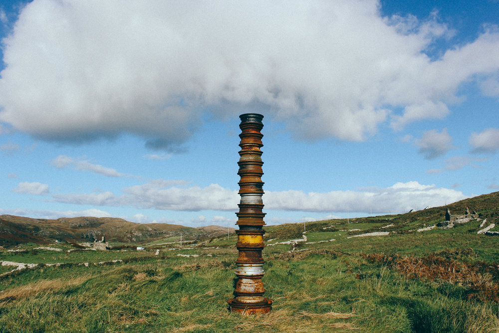 TOTEM A towering monument sited on the North West of the headland overlooking Barley Cove made from stacked tractor wheel rims.