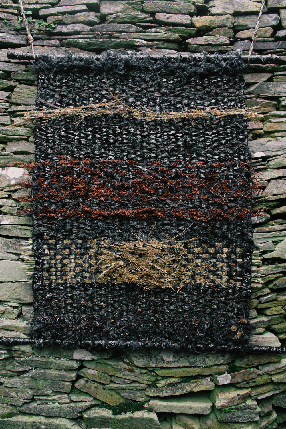 FÍ FIÁIN A woven tapestry using natural and found material hanging inside the copper miners lodge. Materials include seaweed, grasses and Silo wrap.