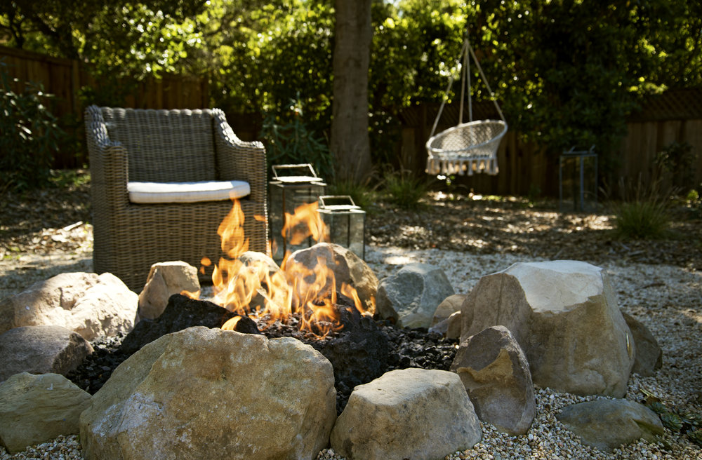 drought tolerant landscape with rustic stone firepit