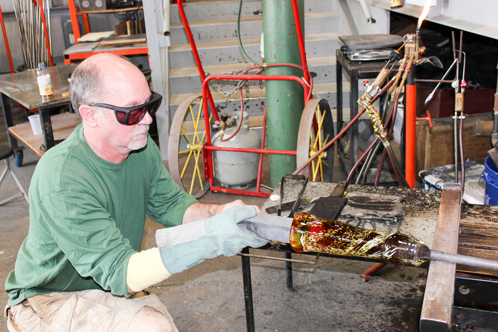 Shaping hot glass with graphite bar.