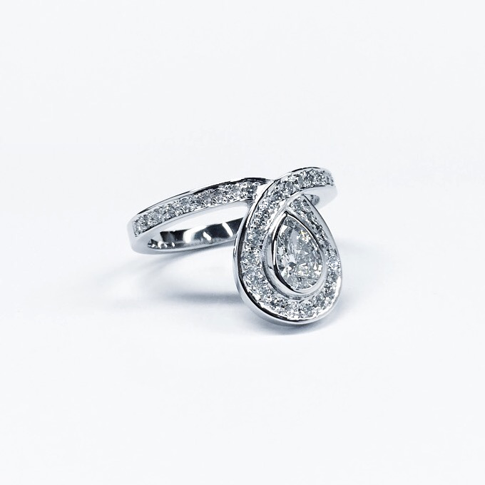 White gold engagement ring set with an incredible pear-shaped diamond surrounded by pave set diamond band.