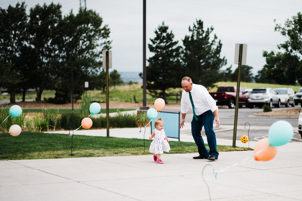father chases is playful daughter outside at Parker Evangelical Presbyterian Church