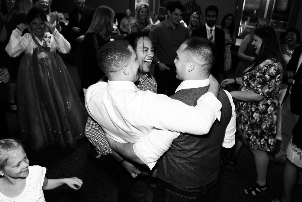 two guests carrying groom onto the dance floor during wedding dance at Parker Evangelical Presbyterian Church