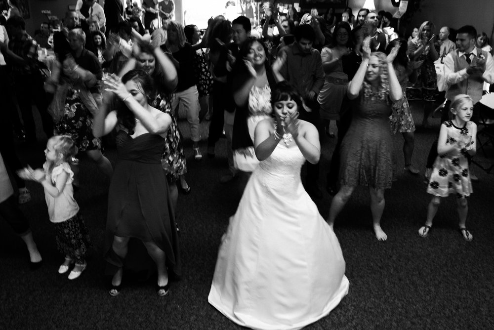 bridge dances in the middle of a crowd during wedding reception at Parker Evangelical Presbyterian Church