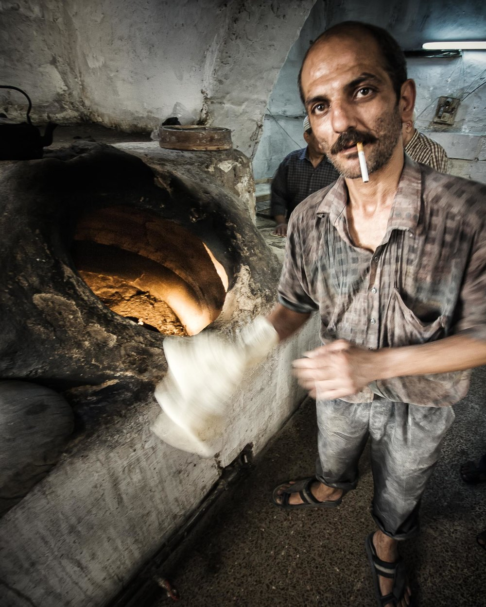 The Baker: Flat slabs of dough is slapped to the inside wall of these kilns to become flat breads (Damascus).