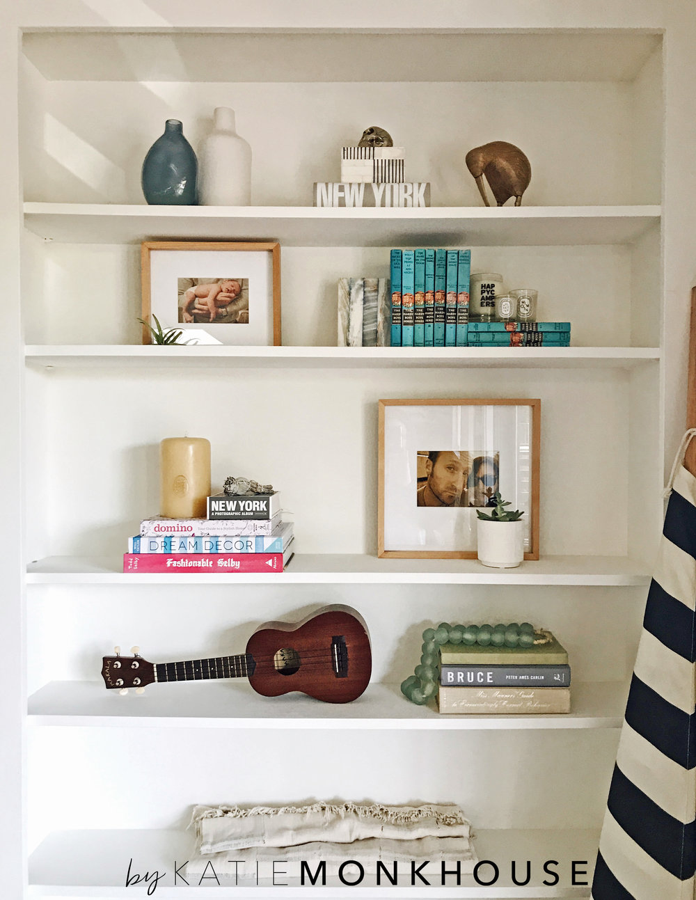 My living room bookcase is ever evolving. TRICK : Put textiles or folded blankets on the lower shelves for 'kid proofing'!