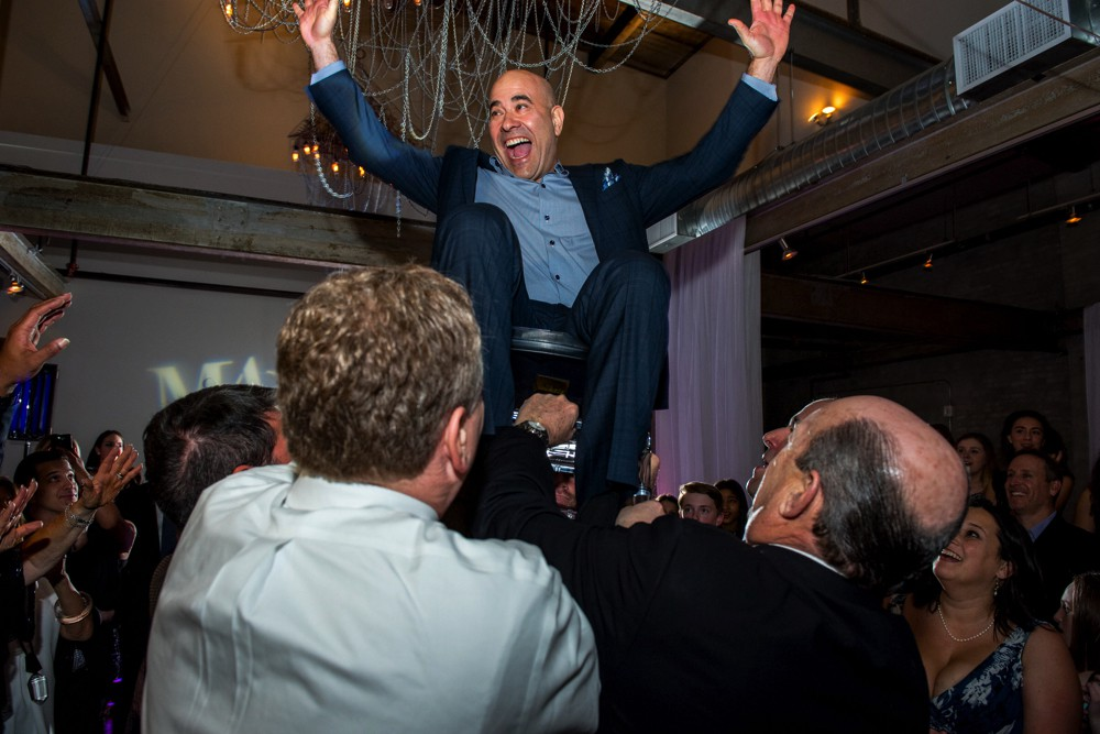 Guy crowd surfing in a chair at a bat mitzvah.jpg