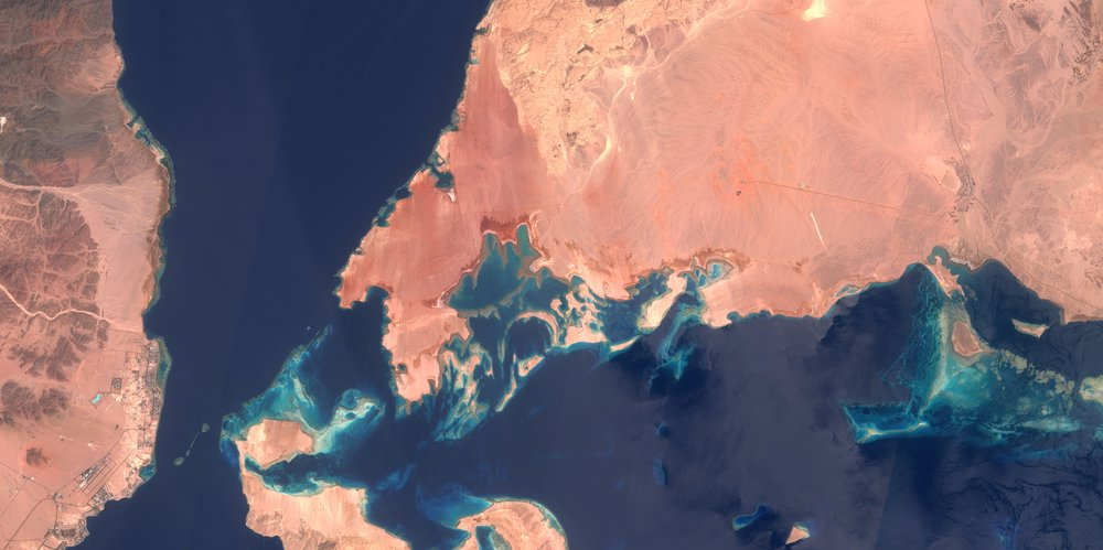 The red sands from the desert offer a visually pleasing contrast with the dark blue from the ocean. The narrow passages between the islands are extremely visible from this angle as rocks and raised ocean floors appear in vivid light blue, highlighting the multiple detours ships would need to take to navigate these waters safely.