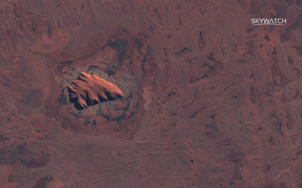 The large Ayers rock forms a distinctive arrow shape of lighter colour in the middle of the red, arid, desertic landscape. On the right of the rock, a small settlement can be seen.