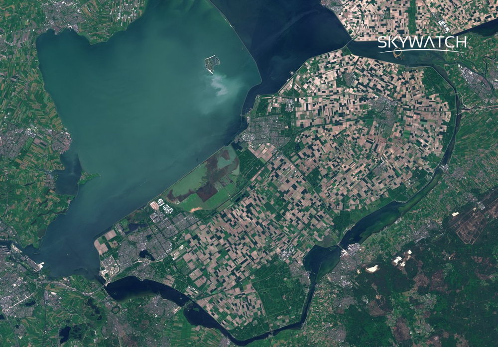 The man-made island visible in the center is separated from the mainland by a canal of dark waters. On the island, numerous agricultural fields can be distinguished, forming a mosaix of black, brown, and green rectangles. North of the island is a large body of water of two different tones of blue. On the outskirts of the images, additional fields can be distinguished.