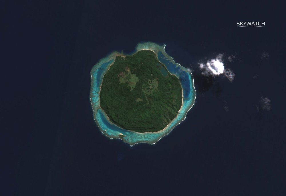The Mago island forms an almost perfect circle of dark green vegetation surrounded by a ring of turquoise waters, broken only at the top of the island. The rest of the image is covered by a dark blue ocean with a small, isolated white cloud on the right side of the image.