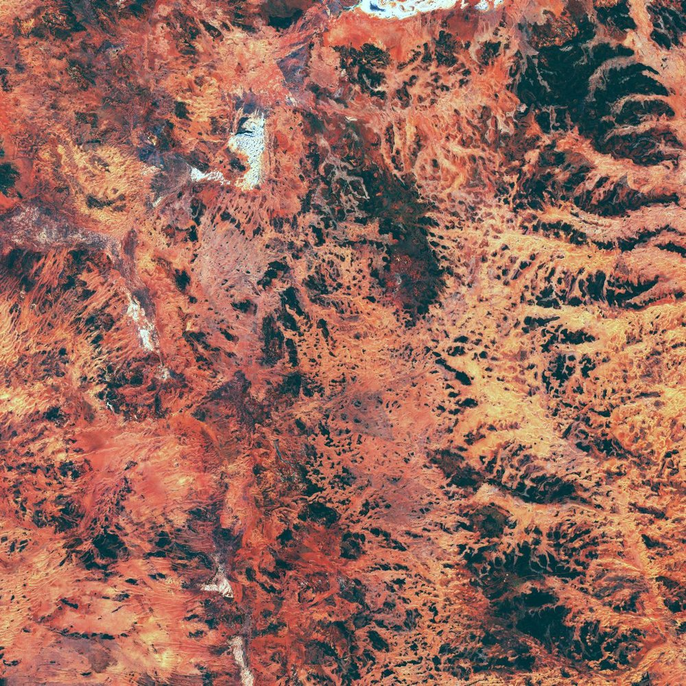 The Gibson desert in Australia shows a vivid range of yellow and red colours, with numerous valleys and crevices.
