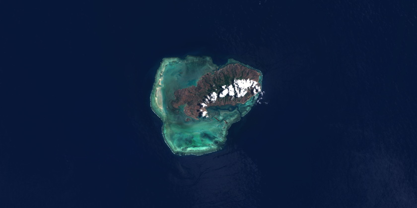 The Rodrigues island offers a stark contrast with the dark blue ocean, thanks to its green and brown lands and surrounding turquoise waters. A few clouds overlooking the island are also visible in this image.