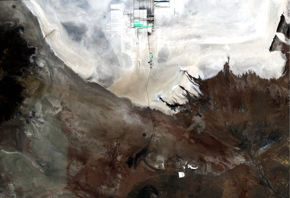 This true-colour composite satellite image shows a very stark contrast between the very white salt plains from Salar du Uyuni and the nearby brown mountainous region. At the top of the image, a salt processing plant creates small black and turquoise blue pools.