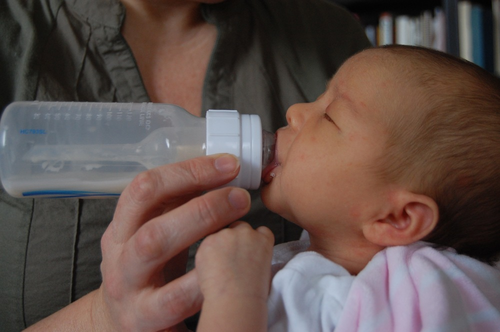 A baby being bottle fed using the Paced Feeding method.