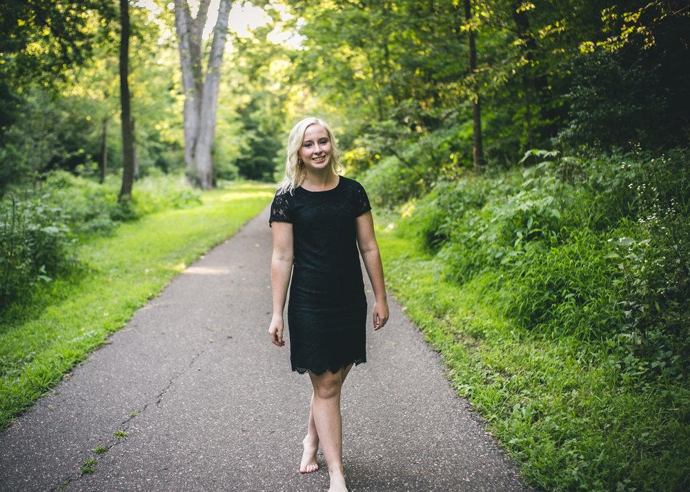 Senior in black dress walks down a path in Stillwater MN