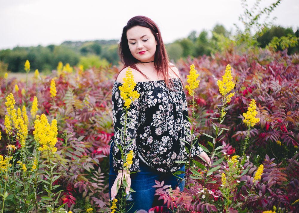 Yellow and red plants in meadow surround high school senior in Hudson WI
