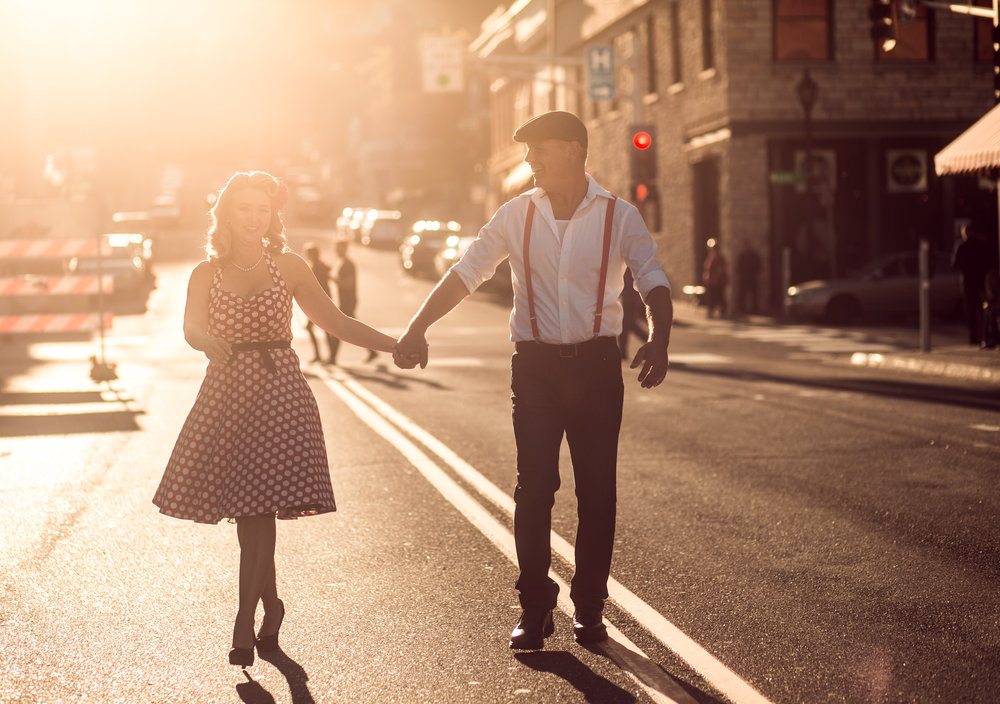 Woman smiles at her fiancé walking down the street holding hands in Stillwater