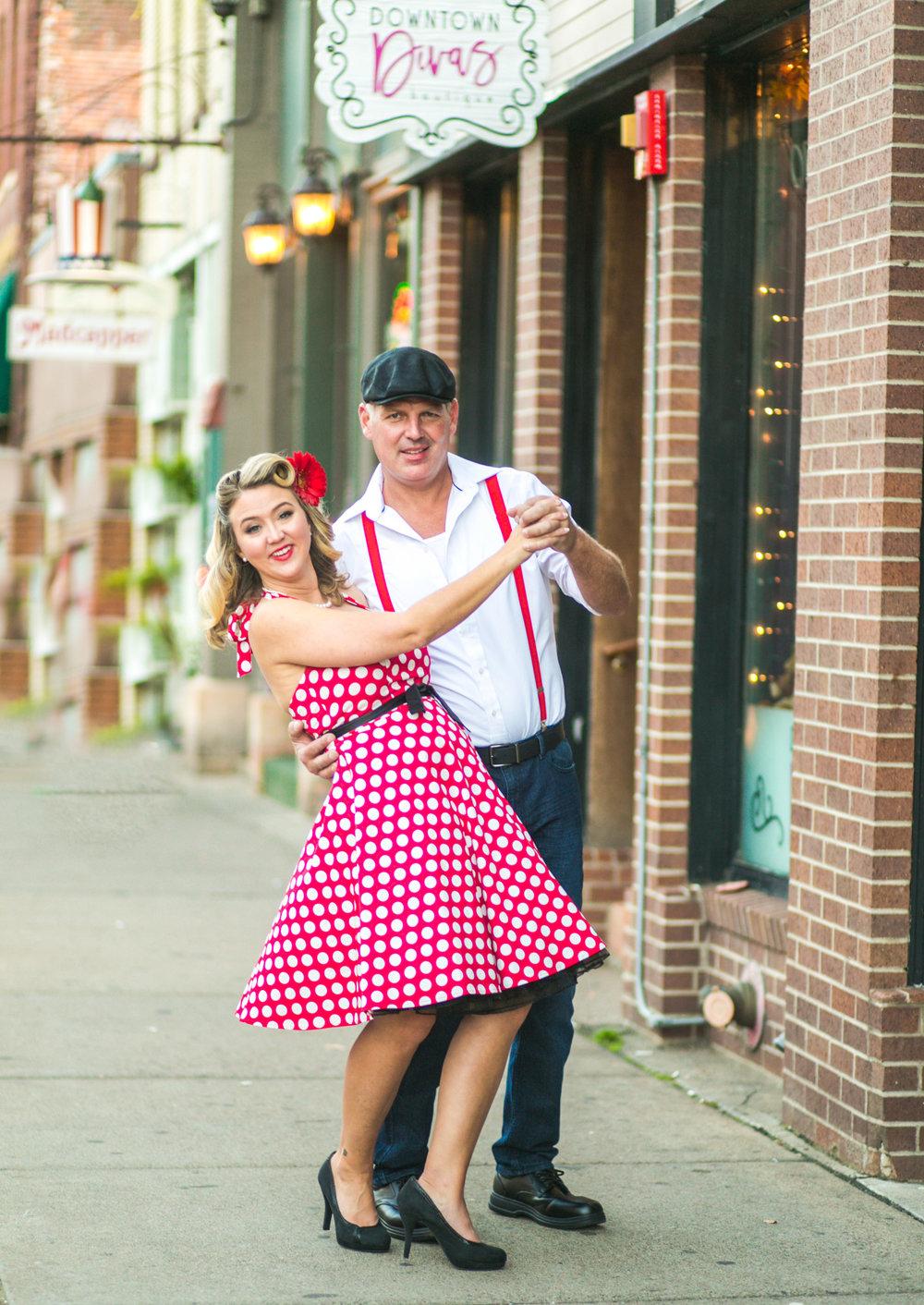 Engaged couple dances on the sidewalk in Stillwater