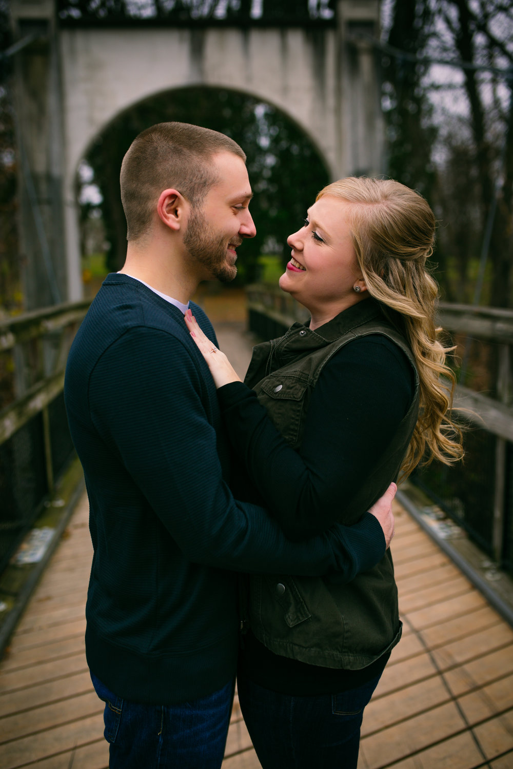 couple smiling and cuddling on Glen Park bridge in River Falls