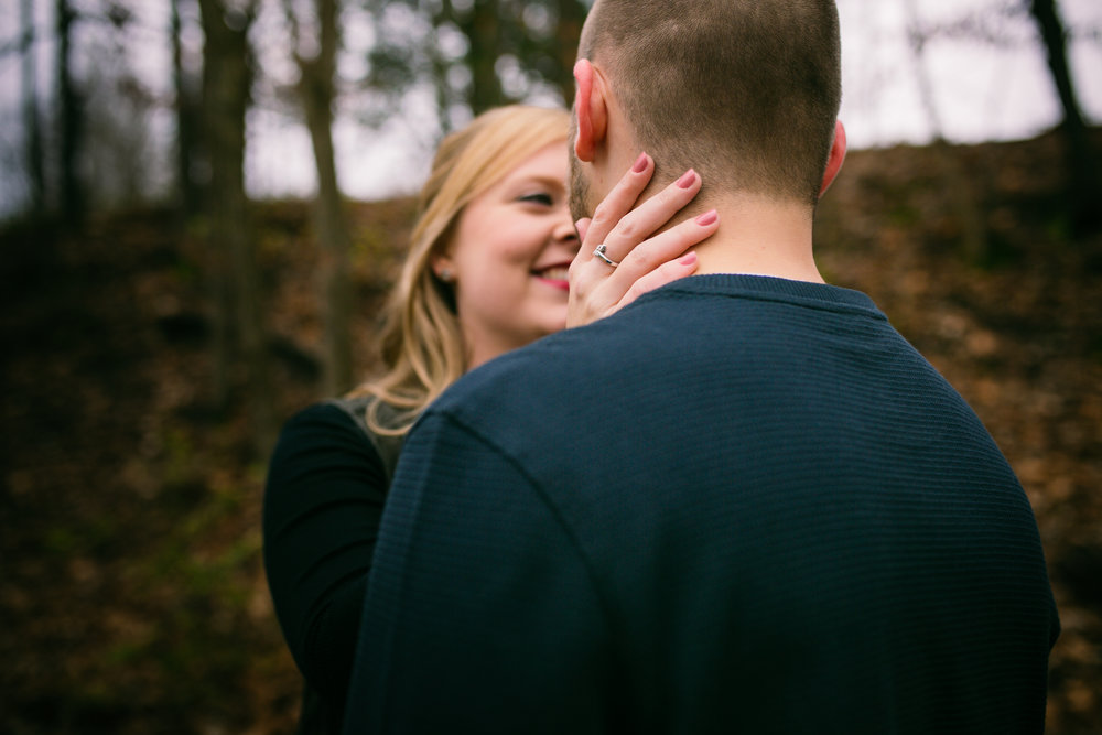 woman smiling at fiancé with hand on neck