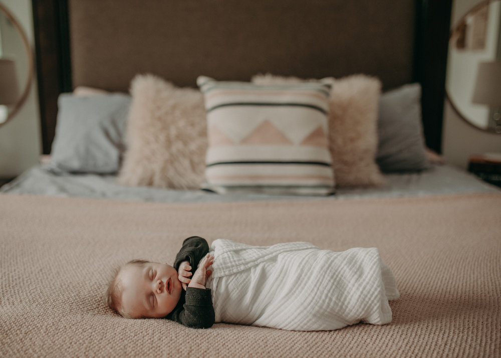 river falls wi baby boy on bed in lifestyle newborn photoshoot