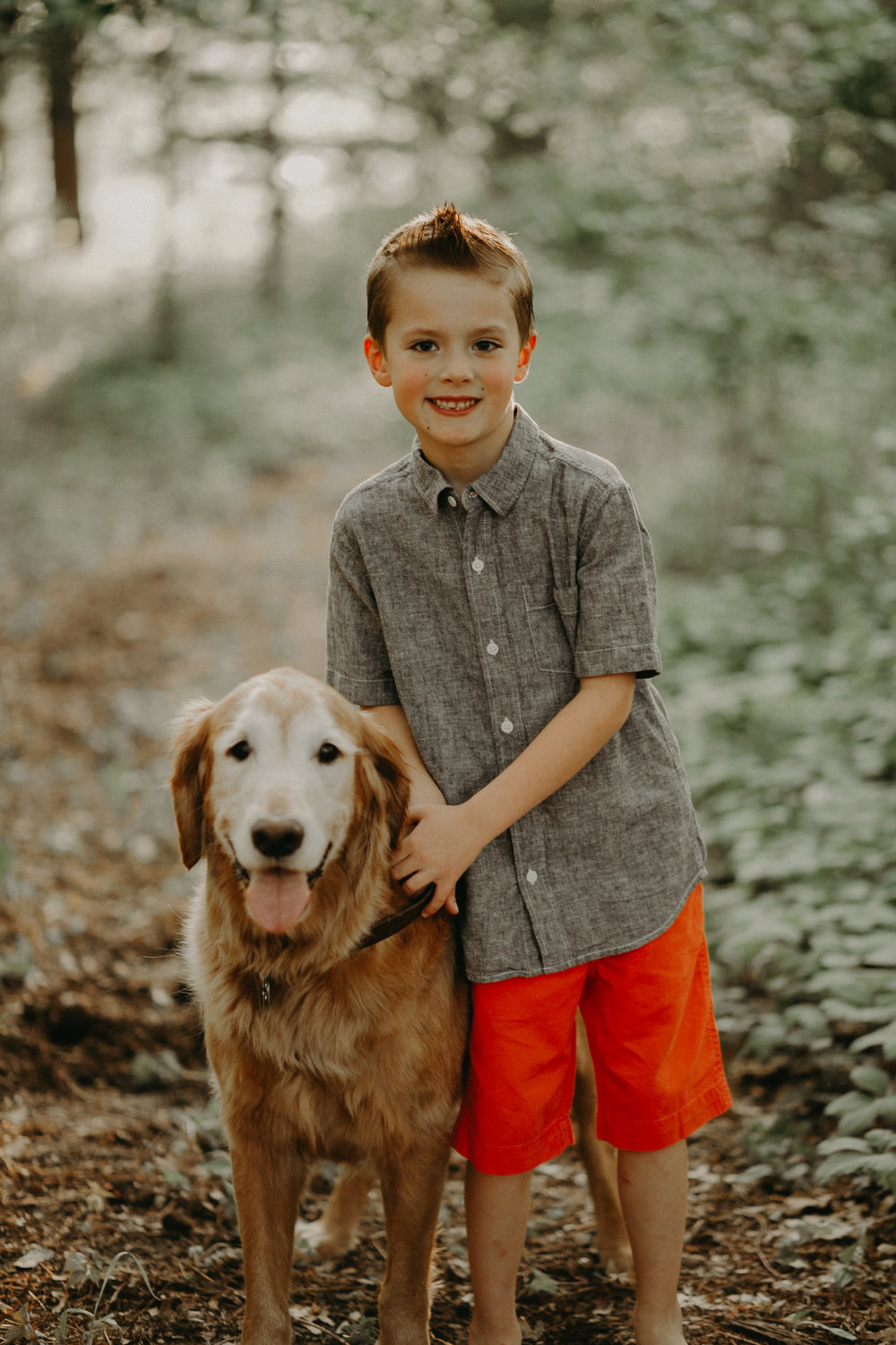 young boy in River Falls WI with Golden Retriever smiling