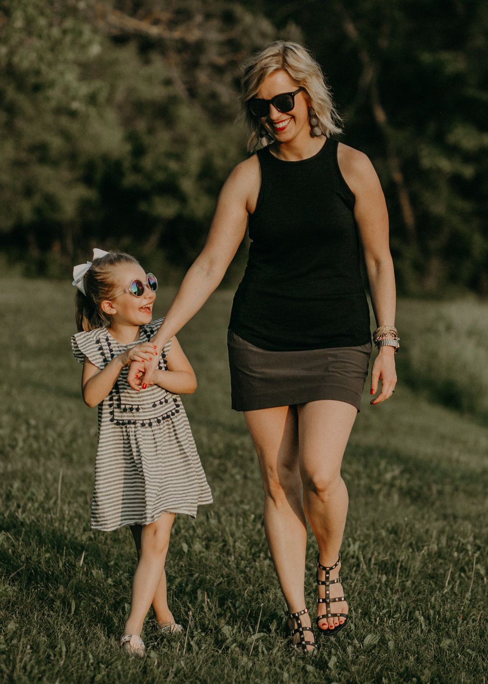 mommy and daughter from River Falls WI walking at sunset and laughing holding hands