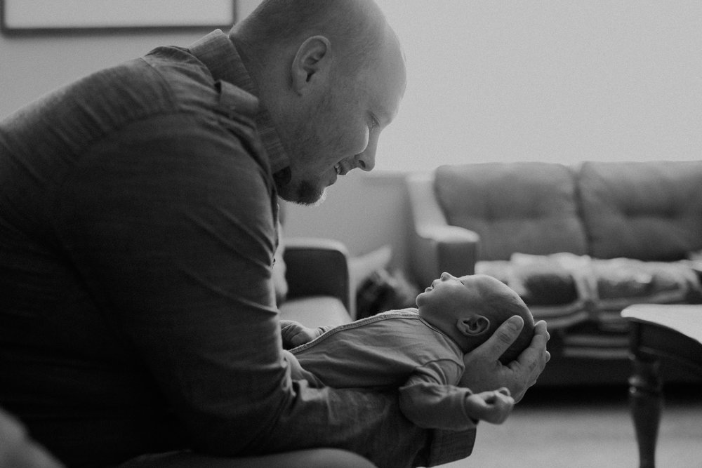 black and white photo of Chaska MN dad holding newborn baby boy in his home