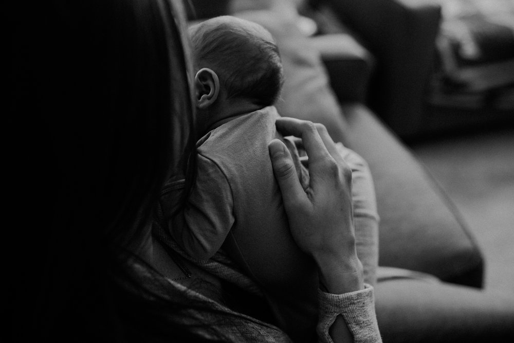 lifestyle image in black and white of mom holding newborn baby boy