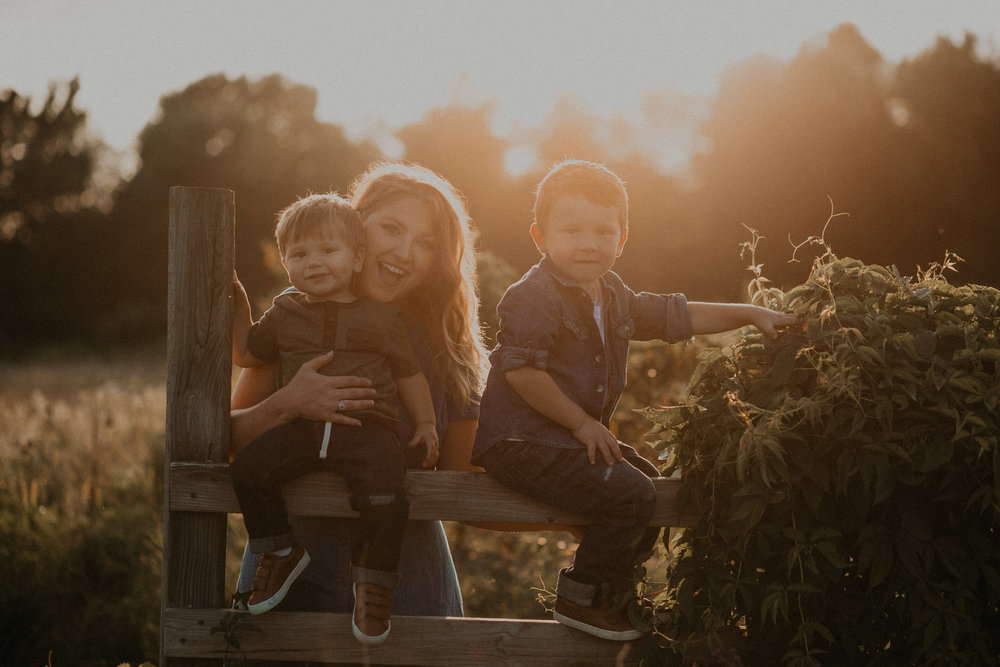 smiling mommy in River Falls Wisconsin during golden hour sunset holding sons