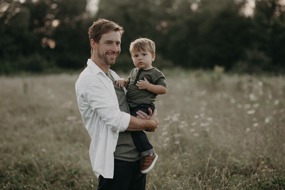 Daddy holding toddler son and smiling in field