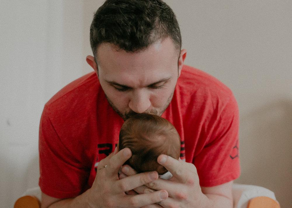 Jared Krasselt kissing newborn baby in Marshfield WI