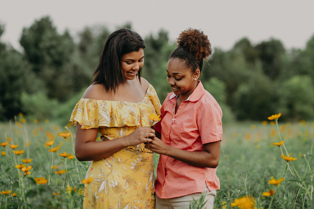 same sex couple of color in a flower field in Hudson WI for a senior session for Andrea Wagner Photography