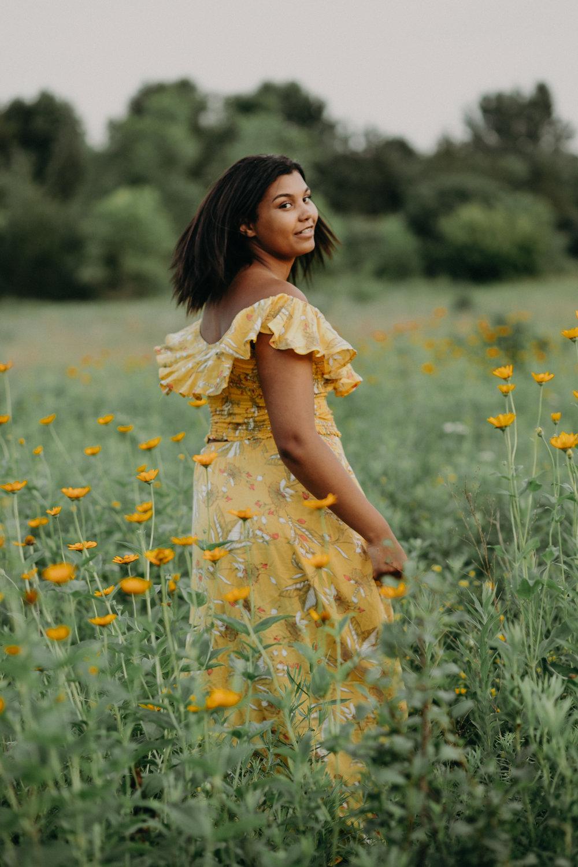 black high school senior from Bloomington MN twirling in a yellow dress in a flower field