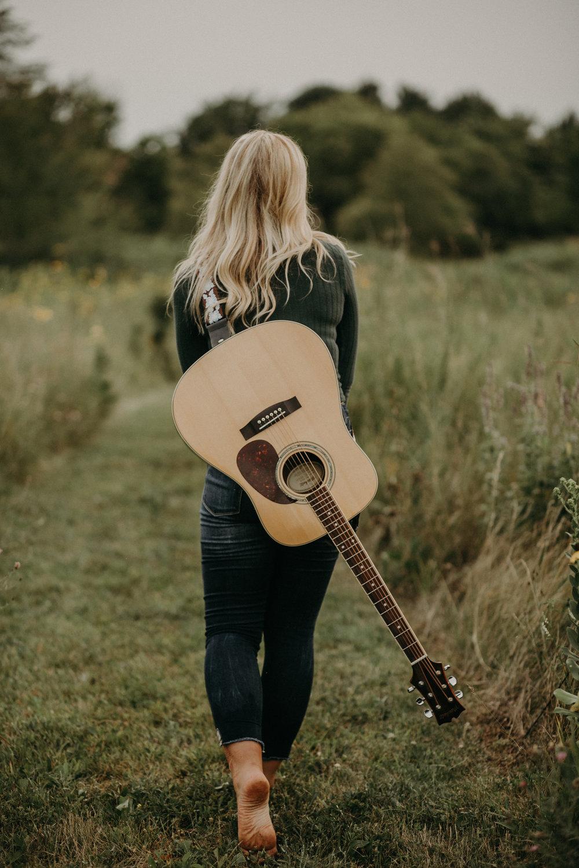 High school senior who plays guitar walking through a field barefoot during her senior photoshoot