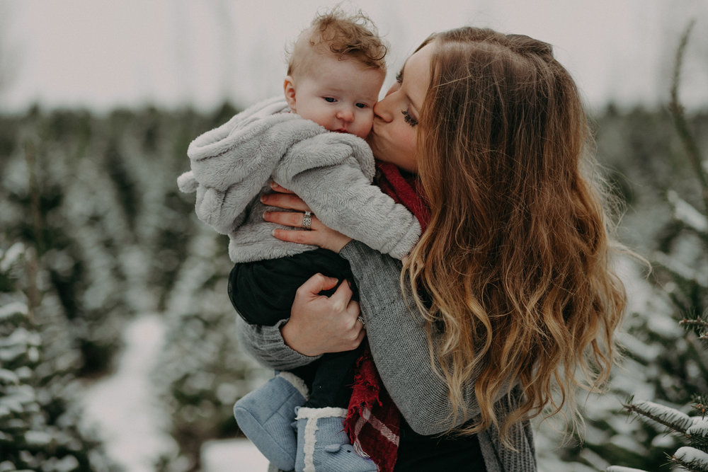 mommy kissing 6 month old daughter during family photo session at Santa's Evergreens in Hudson WI