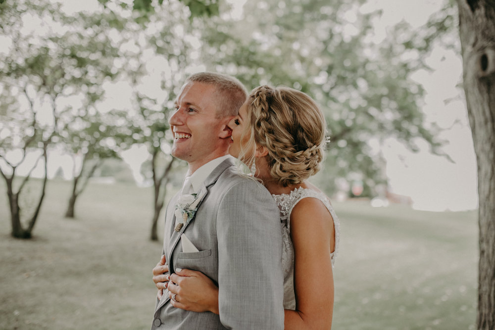wisconsin bride and groom laughing in front of Christ Lutheran Church in Marshfield WI