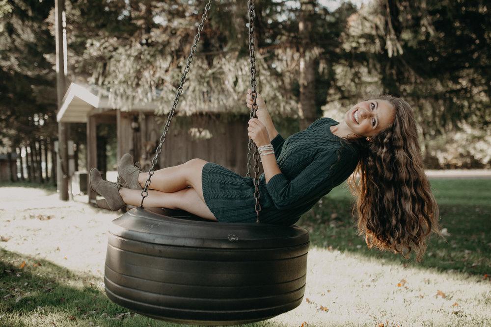 high school senior Dara Stichert swings on a tire swing on Stichert Farms