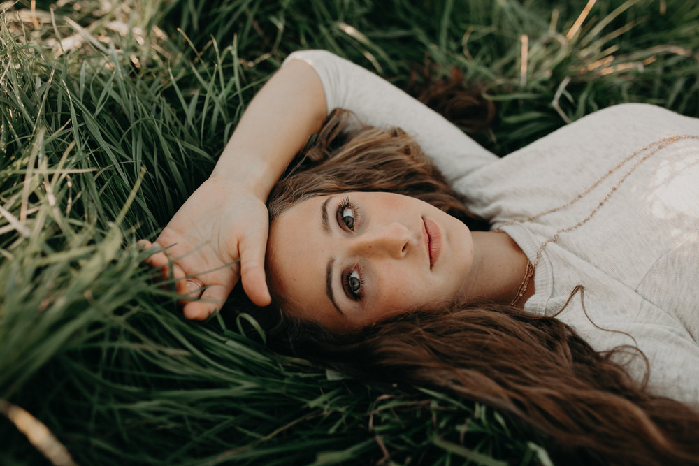 Marshfield High school senior lays in green grass at sunset for senior photos by Andrea Wagner