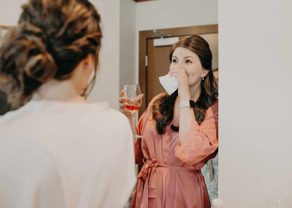 bridesmaid cries as bride gets into her wedding dress at Hotel Landing in Wayzata MN