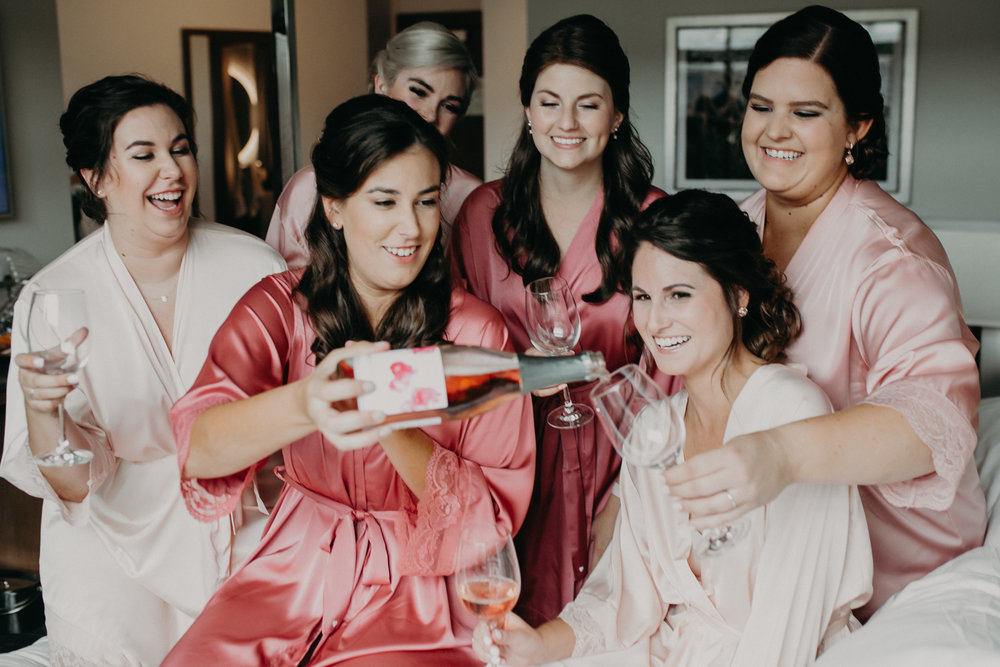 champagne toast by bride and bridesmaids wearing pink robes at Hotel Landing in Wayzata MN