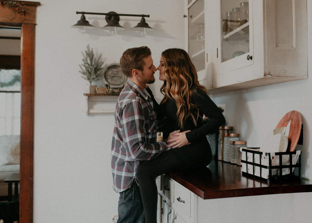 pregnant woman kisses her fiancé in the bright white rustic kitchen during their maternity lifestyle session with Andrea Wagner