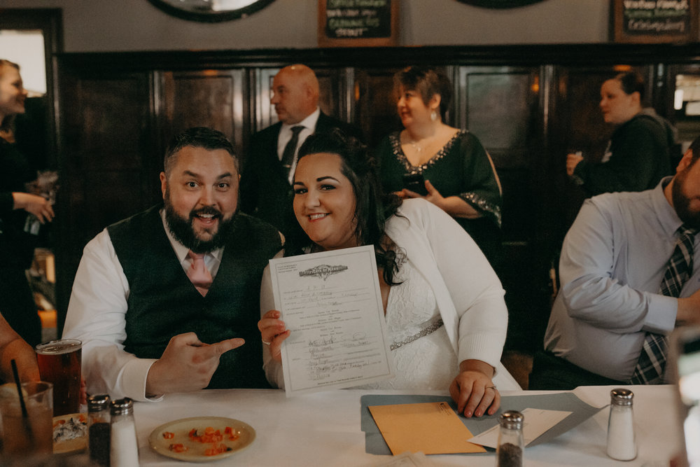 A couple signs their marriage license at Sweeney's Saloon